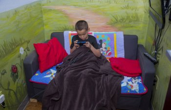 little boy on couch under blanket playing games in recovery room at Smile Structure Dentistry & Braces San Antonio, TX