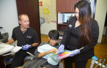 San Antonio TX dentist and dental assistant with a teenage boy in dental chair choosing colored orthodontic elastic ligature