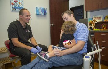 San Antonio, TX dentist talking to father sitting in dental chair with his baby on laps during pediatric dental checkup