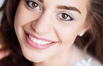 young woman with dark hair showing beatiful teeth in a smile