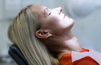 middle-aged woman under sedation in a dental chair