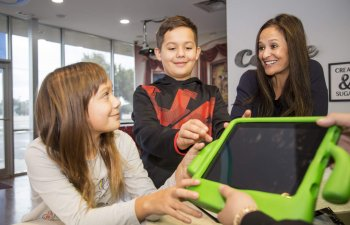 front desk receptionist passing iPad to children patients at Smile Structure Dentistry & Braces San Antonio, TX