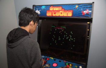 a boy playing Arcade Games in a dentist waiting room at Smile Structure Dentistry & Braces San Antonio, TX